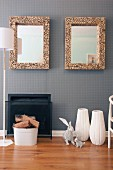 Hare ornaments in front of white floor vases next to open fireplace and bucket of logs; two framed mirrors on wall with grey wallpaper