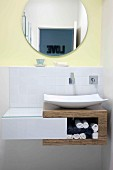 Washbasin on wooden shelf base unit with white drawer; round mirror on wall painted pale yellow