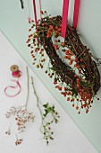 Kranz aus Weiden- und Hagebuttenzweigen an roter Schleife aufgehängt