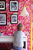 Child sitting at desk, standard lamp with nostalgic fabric lampshade and yellow-painted base, family photos on pink wallpaper with floral pattern