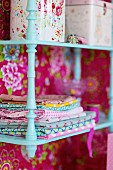 Storage boxes and linen on wall-mounted shelves painted pale turquoise