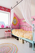 Canopy bed with turquoise, retro metal frame and curtains draped from rods hung from ceiling in nostalgic child's bedroom