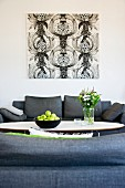 Fruit bowl on classic coffee table between grey sofas and black and white graphic artwork on wall