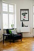 Black armchair and side table on herringbone parquet floor below window in period apartment