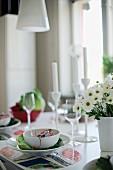 Gedeck mit weisser Schale auf Tischset, seitlich teilweise sichtbarer Blumenstrauss in Vase
