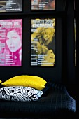 Detail of bed with yellow and black and white patterned scatter cushions on black throw and collection of posters on wall