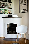Classic-style, white shell chair with wooden frame next to open fireplace in rustic interior