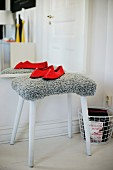 Red slippers on stool with grey, fur-like cover in front of mirror on wall