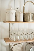 Storage jars, wicker basket and glasses on wooden shelves on white wooden wall