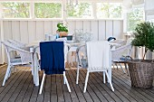 Seating area with white wicker chairs next to small tree in basket on wooden floor of wood-panelled veranda