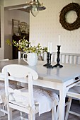 White kitchen chair with curved backrest at dining table and wicker wreath on wall in rustic interior