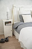 White wooden bedside table next to bed with tall headboard and grey and white bed linen