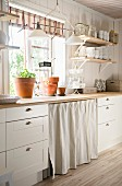 White country-house kitchen with worksurface below window