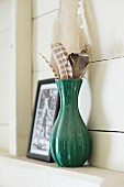 Collection of feathers in green ceramic vase on shelf