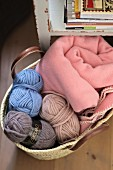 Balls of wool in various colours and pink blanket in basket on floor