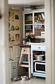 View into kitchen with rustic plant stand, base unit and glass-fronted wall units