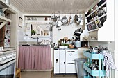 Retro tea trolley below shelves on wall and sink unit next to cooker in rustic kitchen