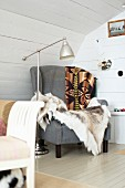 Comfortable grey armchair with fur blanket and retro standard lamp in corner of room with white wooden walls
