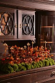 Festive arrangement of red berries, brass tealight holders and moss on base unit of dresser