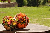 Autumnal flower arrangements in polystyrene bowls covered in lentils on wooden table outdoors