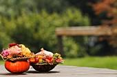 Autumnal flower arrangements in hollowed-out pumpkins outdoors