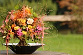 Autumnal, colourful bouquet of garden flowers in bowl