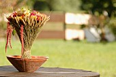 Bouquet of flowers and ears of wheat in clay bowl on garden table