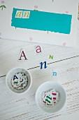 Briefumschlag selbst gestalten - Papier Buchstaben auf Holzunterlage und in weissen Porzellanschalen sortiert