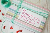 Hand-crafted label with stamped address on gift wrapped in striped pastel paper with matching ribbon