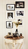 Framed black and white family photos above antique console table with marble top