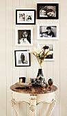 Gerahmte Familienfotos in Schwarzweiss über antikem Konsolentisch mit Marmorplatte