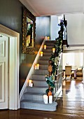 Lit candles on stair treads in hallway of traditional, elegant villa with view into living room through floor-to-ceiling open doorway