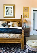 Elegant double bed with carved wooden frame and Oriental-style stool in bedroom