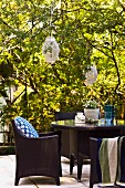 Dark modern outdoor chairs and table on terrace in garden of old villa with lanterns hanging from trees