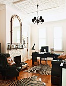 Open fireplace, stucco ceiling, zebra-skin rugs on wooden floor in front of desk in grand study