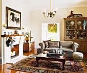 Antique coffee table and sofa on Oriental rug in traditional living room with open fireplace