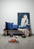 Selbst gefärbte Indigo-Kissen und Gemälde mit Frauenakt auf bespannter Bambusliege, davor ein Beistelltisch aus Acrylglas