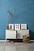 Vintage arrangement of white locker against blue-grey wall and three DIY string art pictures