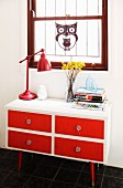 Red, retro table lamp on 50s-style, white chest of drawers with red drawer fronts below decorative ornament hung in window