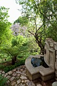 Concrete fountain against stone wall in woodland-style garden