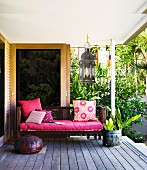 Bench with deep pink seat cushion and scatter cushions on wooden decking; tropical plants in background