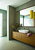 Washstand with basin on wooden base unit and large mirror on grey tiled wall in modern bathroom