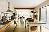 Kitchen counter and large table with stone worksurface next to open, folding glass door