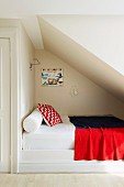 Bolster, scatter cushions and blanket on bed in niche below sloping attic ceiling