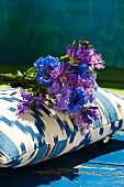 Posy of cornflowers on blue and white patterned cushion