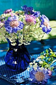 Cobalt blue glass vase of violet scabious and cow parsley on blue fabric with white polka dots