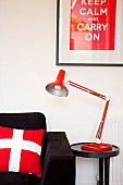 Red and white accessories combined with black sofa - Swiss flag scatter cushion and framed poster with motto above side table and reading lamp