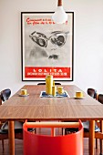 Framed, vintage poster decorating wall above table set with simple, yellow, retro coffee set