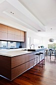 Designer kitchen in light-flooded interior; long counter with wooden fronts and breakfast bar surface on one corner