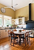 Large, high-ceilinged country-house kitchen with station clock on yellowy beige wall panelling, vintage gas stove with black extractor hood and antique dining set in centre